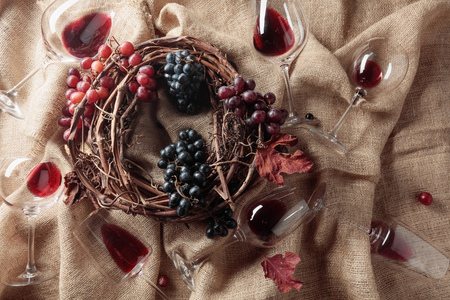 Red wine and grapes on a table covered with burlap. Top view.