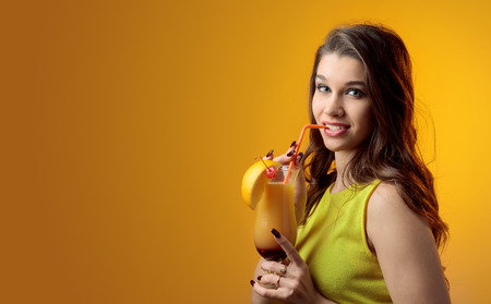 Young beautiful girl in a yellow dress with cocktail Tequila Sunrise. Copy space. Standard-Bild