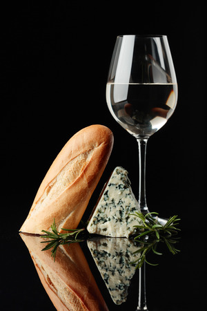 Blue cheese with bread, rosemary and white wine on a black reflective background. Copy space for your text.