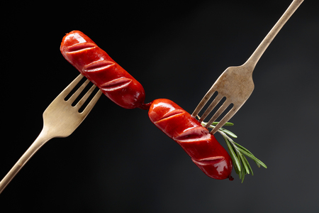 Grilled sausages with rosemary on a forks. Black background, copy space.