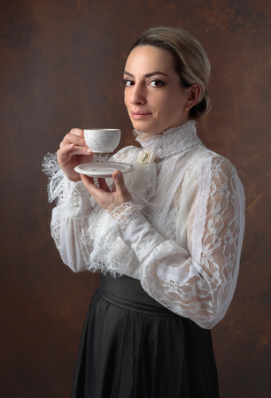 Portrait of a woman in Victorian clothes with a cup of coffee. White blouse with lace, embroidery and high collar.