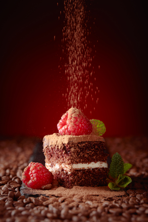 Chocolate cake with raspberry and mint sprinkle with cocoa powder. Coffee beans are scattered on the table.