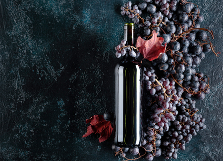 Bottle of red wine and grapes on a dark blue background, top view, copy space for your text.