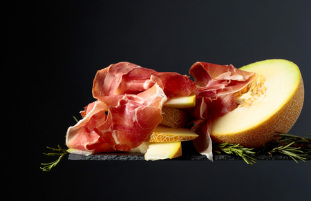 Prosciutto with melon and rosemary  on a black background, copy space.