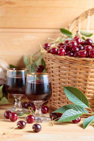 Cherry wine or liquor on wooden background and ripe juicy cherries in basket.