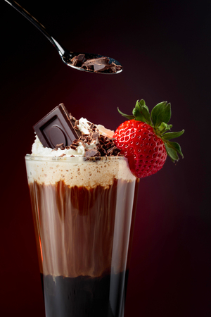 Chocolate drink with whipped cream, strawberry and pieces of black chocolate on a dark background. Copy space.