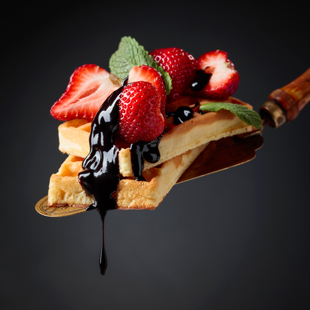 Belgian waffles with strawberries, mint and chocolate sauce on a black background. Copy space. Imagens