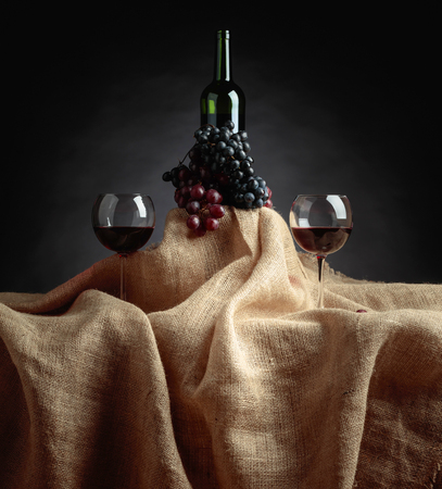 Red wine and grapes on a table covered with burlap. 写真素材