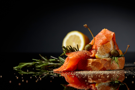 Sandwich with trout fillet, lemon slice, capers and rosemary sprinkle with pepper. Black reflective background. Copy space.