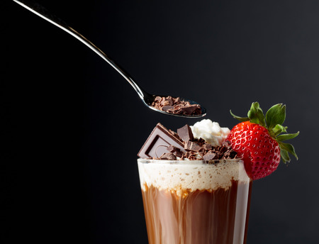 Chocolate drink with whipped cream, strawberry and pieces of black chocolate on a dark background. Copy space. Stockfoto