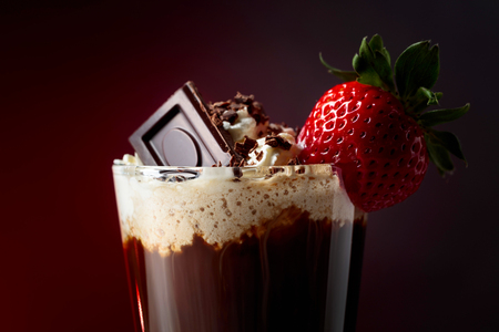 Chocolate drink with whipped cream, strawberry and pieces of black chocolate on a dark red background. Copy space.