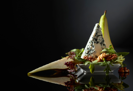 Blue cheese with walnuts, pear and greens on a black background.