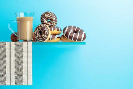 Chocolate donuts and latte on a blue background. Copy space for your text. Archivio Fotografico