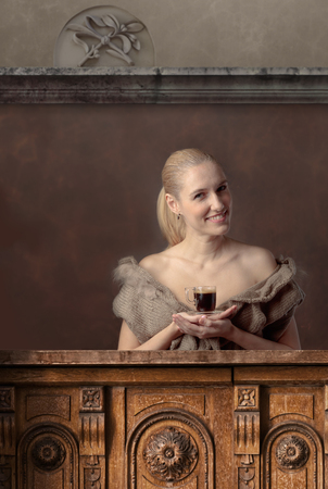 Attractive and happy blonde in a sweater with a cup of coffee at the bar.