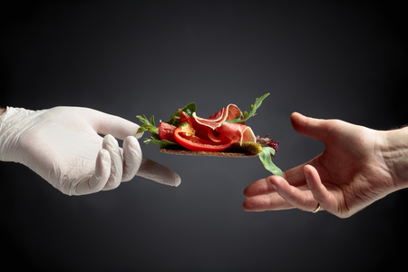 Conceptual image on the theme of fine food and delicacies. Rye cracker with prosciutto, tomato, paprika and cornichon garnished with greens. Compliment from the chef.