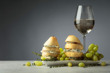 Blue cheese with pear and glass of white wine. Cheese with pear, thyme and grapes on a kitchen table. Copy space.