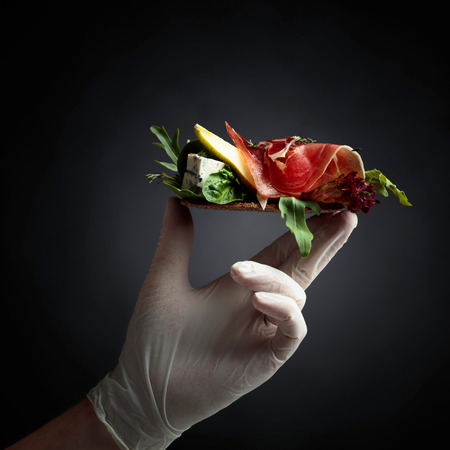 Conceptual image on the theme of fine food and delicacies. Rye cracker with blue cheese, prosciutto and pear garnished with greens. Compliment from the chef.