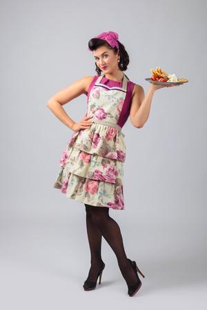 Piękna młoda gospodyni domowa w fioletowej sukience i fartuchu. Ekspresyjna mimika twarzy. W ręku belgijskie gofry z truskawkami i śmietaną. Zdjęcie Seryjne