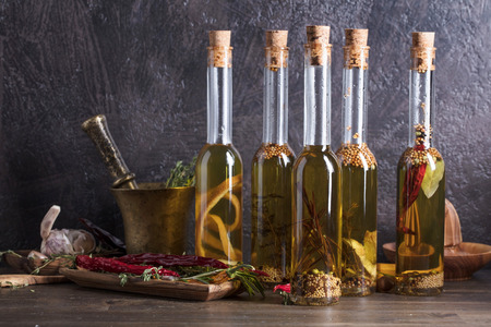 Bottles of olive oil on a old wooden table. Olive oil with different spices and herbs.