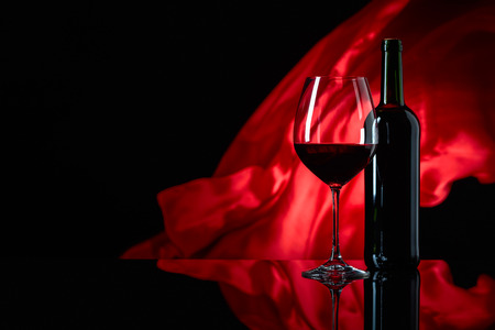 Wineglass and bottle of red wine on a black reflective background. Red satin curtain flutters in the wind. Copy space.