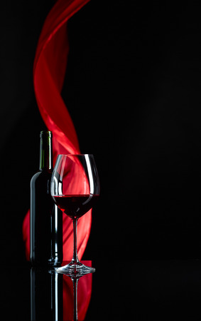 Wineglass and bottle of red wine on a black reflective background. Red satin curtain flutters in the wind. Copy space. Kho ảnh - 122399601
