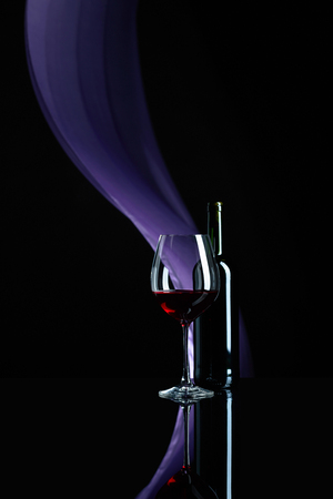 Wineglass and bottle of red wine on a black reflective background. Purple satin curtain flutters in the wind. Copy space.