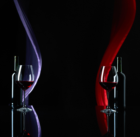 Red wine on a black reflective background. Satin curtain flutters in the wind. Copy space.