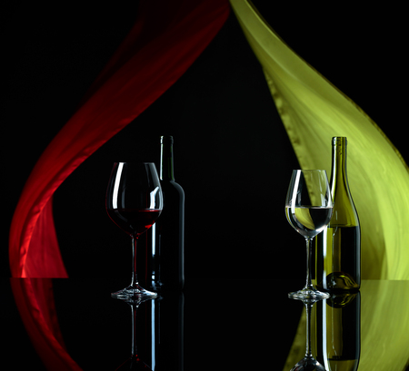 Red and white wine on a black reflective background. Satin curtain flutters in the wind. Copy space.