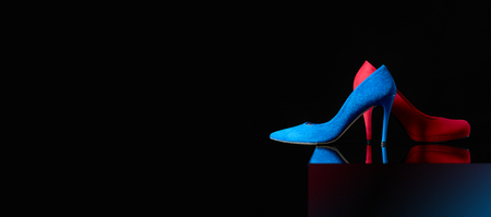 Blue and red womens corduroy shoes on a black background. Copy space. Фото со стока