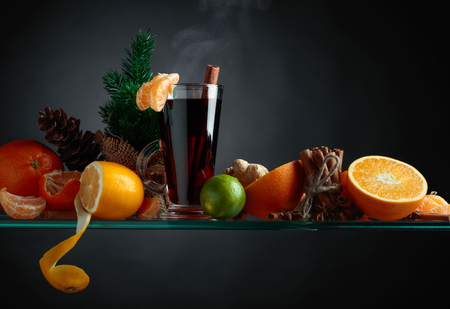 Mulled wine hot drink with citrus and spices. Copy space for your content.