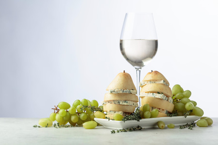Blue cheese with pear and glass of white wine. Cheese with pear, thyme and grapes on a kitchen table. Copy space. Banque d'images - 122712728