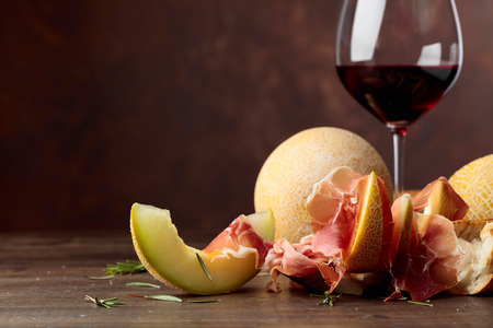 Glass of red wine and mediterranean snacks. Prosciutto with melon and rosemary on a old wooden table, copy space. 写真素材