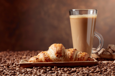 Coffee latte and croissant on a table with coffee beans. Copy space.