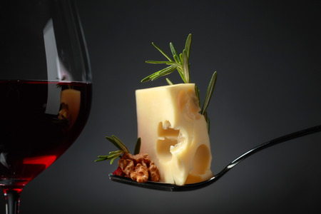 Maasdam cheese with walnuts, rosemary and red wine on a black background. Copy space.