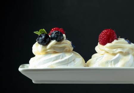 Small cake dessert Pavlova with blueberries and raspberries on a black background. 写真素材