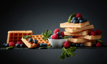 Waffles with  blueberries, raspberries  and  mint a dark background. Copy space.