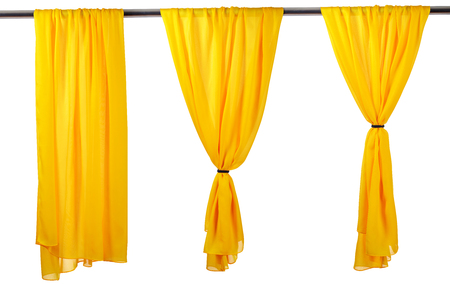 Vertical yellow satin curtains isolated on white background. Reklamní fotografie