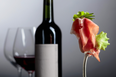 Prosciutto with rosemary and red wine on a grey background. Фото со стока