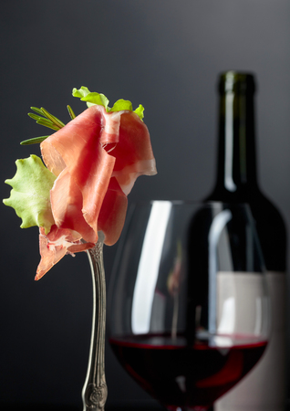 Prosciutto with rosemary and red wine on a dark background. Фото со стока - 122748945