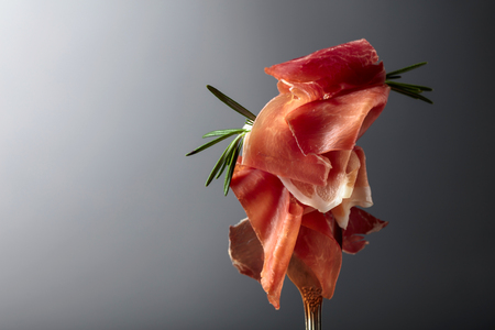 Prosciutto with rosemary on a grey background. Фото со стока
