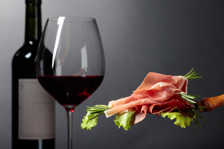 Prosciutto with rosemary and red wine on a grey background. Imagens