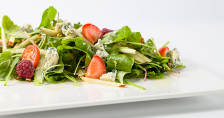 Green salad with Gorgonzola and berries on a white plate.