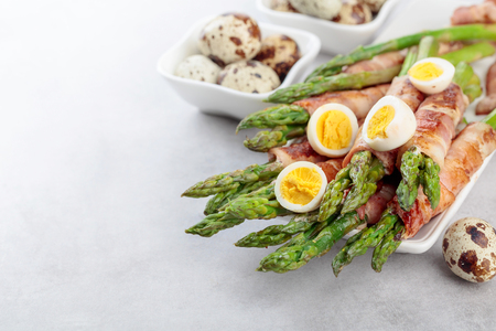 Asparagus with bacon. Green asparagus wrapped in bacon with boiled quail eggs. Copy space.
