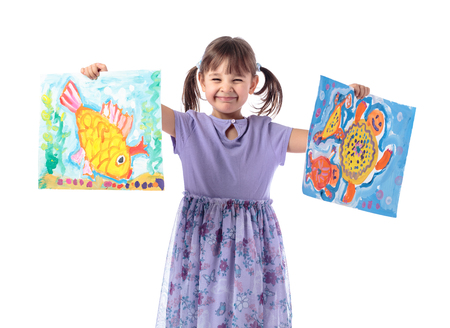 Happy girl in a purple dress shows her drawings. The drawings show a goldfish and a turtle. Isolated on white background.