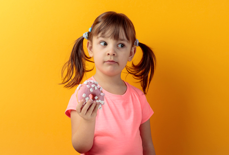 Girl in a pink t-shirt eat donut and look to right. The girl's hair is tied in tails. Copy space. Banco de Imagens