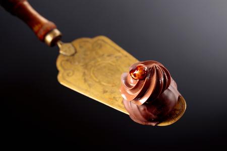 Chocolate dessert with cream and hazelnut on a cake spatula.