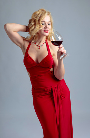 Attractive smiling mature woman in red evening dress with glass of red wine.  Happy forty years blonde on a white background.