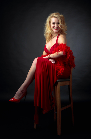 Attractive smiling mature woman  in red evening dress with fluffy feather boa. Happy forty years blonde on a black background. Stock Photo