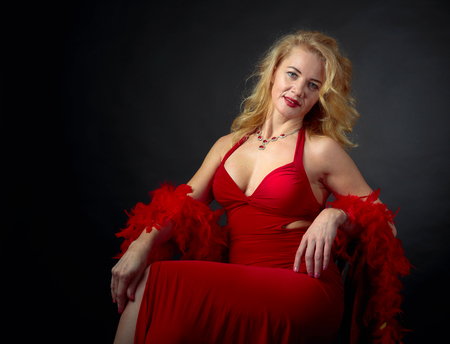 Attractive smiling mature woman  in red evening dress with fluffy feather boa. Happy forty years blonde on a black background. Copy space.