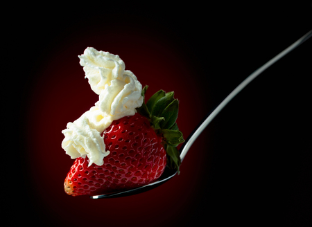 Strawberry with whipped cream in spoon on a dark background. Copy space.